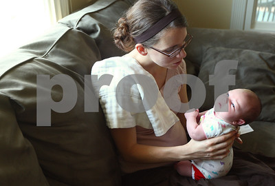 Kyle Bursaw – kbursaw@shawmedia.com  Doula Kim Wheaton holds client Chrissy Deming's two-week-old daughter Abby on Deming's DeKalb home on Friday, May 25, 2012.