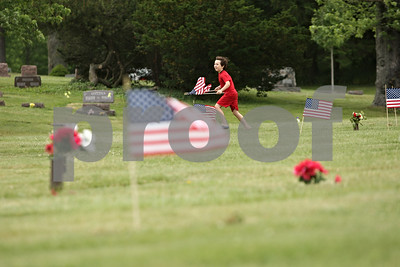 Rob Winner - rwinner@shawmedia.com  Coby Sexton, 8, of Cub Scout Pack 131 in DeKalb, looks for the graves of veterans to place a U.S. flag Saturday morning at  Fairview Park Cemetery in DeKalb. Multiple scouts helped in the effort as part of an annual tradition before Memorial Day services.