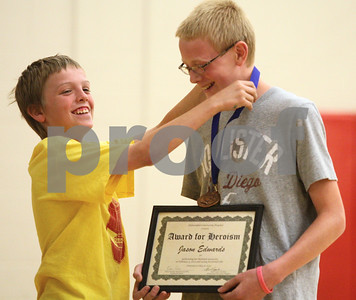 Kyle Bursaw – kbursaw@shawmedia.com  Austin Benson puts a medal over the neck of Jason Edwards during an assembly at Sycamore Middle School on Thursday, May 31, 2012. Jason used the Heimlich maneuver in February to attempt to dislodge an Atomic Fireball Austin choked on while the two, along with Austin's older brother Dylan, had a contest to see who could keep the candy in their mouth the longest on February 3, 2012.