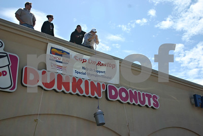 (Left to right) Local law enforcement officers Joel French, Naomi Faivre and Jon Jursich watch Friday as Thomas Hackler pulls a donation bucket onto the roof of Dunkin' Donuts on DeKalb Avenue during the Cops on the Rooftop event, which benefits Special Olympics Illinois.  Caitlin Mullen - cmullen@shawmedia.com