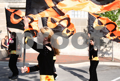 Kyle Bursaw – kbursaw@shawmedia.com  Quinn Patterson (foreground) and the rest of the color-guard leading the DeKalb High School marching band in the parade make their way down Third Street in DeKalb on Monday, May 28, 2012.