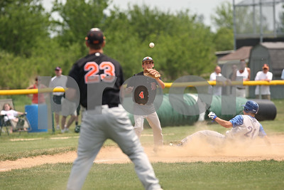 Rob Winner – rwinner@shawmedia.com  After fielding a sacrifice bunt, DeKalb pitcher Corey Nelson (23) throws to third baseman Patrick Aves (4), but not before Marmion Academy baserunner Connor Medernach slides safely into the bag in the bottom of the fourth inning during the Class 3A Kaneland Regional final in Maple Park Saturday afternoon. Marmion Academy defeated DeKalb, 4-1.