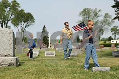 Rob Winner – rwinner@shawmedia.com  Sean Mays (center) and his two boys, Ryan (left), 5, and Andy (right), 9, of Cub Scout Pack 131 in DeKalb, look for the graves of veterans to place a U.S. flag Saturday morning at  Fairview Park Cemetery in DeKalb. Multiple scouts helped in the effort as part of an annual tradition before Memorial Day services.  DeKalb, Ill. Saturday, May 26, 2012