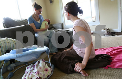Kyle Bursaw – kbursaw@shawmedia.com  Doula Kim Wheaton (right) looks on during a follow-up appointment as Chrissy Deming interacts with her two-week-old daughter Abby at Deming's DeKalb home on Friday, May 25, 2012.