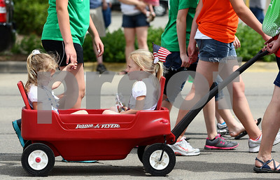 Kyle Bursaw – kbursaw@shawmedia.com  Three-year-old twins Lexie (left) and Lizzie Rothenbach get a ride in Sycamore's Memorial Day parade on Monday, May 28, 2012.