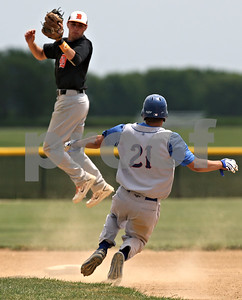 Rob Winner – rwinner@shawmedia.com  DeKalb second baseman Kevin Sullivan (left) makes a leaping catch after a throw from third baseman Patrick Aves (not pictured) before tagging out Marmion Academy baserunner Connor Mederrnach (21) in the bottom of the fifth inning during the Class 3A Kaneland Regional final in Maple Park Saturday afternoon. Marmion Academy defeated DeKalb, 4-1.