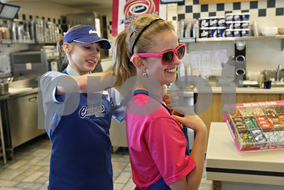 Rob Winner – rwinner@shawmedia.com  Courtney Nelson (left) helps Hayley Foord, 14, with her apron at Culver's in Sycamore Tuesday evening. Foord is raising money for this weekend's Relay for Life event. Culver's agreed to donate 10% of their profits to Foord's team, Hayley's Hi Hopes, during a three-hour span Tuesday night.
