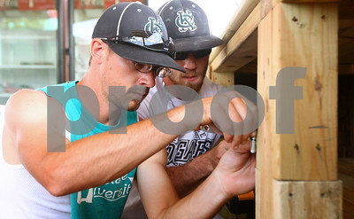 Kyle Bursaw – kbursaw@shawmedia.com  DeKalb County Liners Assistant General Manager Garrett Jones (front) and his brother Nathaniel Jones put in the hinges for a cabinet door in the food stand that operates during Liners games at Sycamore Park on Tuesday, May 29, 2012.