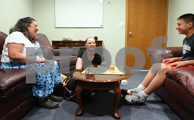 "Kyle Bursaw – kbursaw@shawmedia.com  Robin Waffle (left) shares a laugh while plays a counseling board game called ""The Talking, Feeling, Doing Game"" in a session with Dakota Klotz, 11, (right) and his mother Heather Klotz (center) at the DeKalb Youth Services Bureau on Thursday, May 10, 2012."