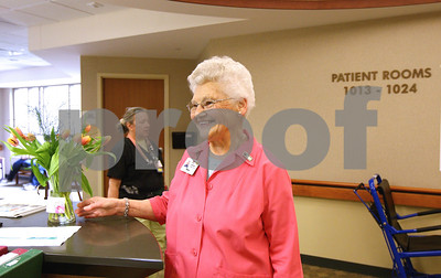 Kyle Bursaw – kbursaw@shawmedia.com  Kishwaukee Community Hospital volunteer Mina Johnson brings flowers from the front desk to one of the desks within the hospital on Wednesday, May 9, 2012. Johnson has been volunteering at the hospital for 15 years.