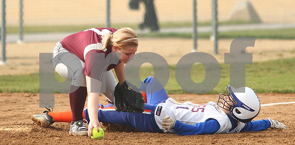 Kyle Bursaw – kbursaw@shawmedia.com  Genoa-Kingston's Emily Wakely slides in safely between the legs of a Marengo player who did not make the catch at third in the second inning of the Cogs 7-5 loss to Marengo in Genoa, Ill. on Tuesday, May 1, 2012.