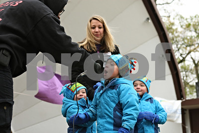 Rob Winner – rwinner@shawmedia.com  Elizabeth Elie (far left) holds the microphone for Brodin Kuhl, 3, who addresses the crowd before the March for Babies event at Hopkins Park in DeKalb Saturday morning. Kuhl's family, including brothers Trevin (left) and Gavin (right) and their mother Kalie Kuhl, is the Ambassador Family for the DeKalb County 2012 March for Babies. The triplets were born 8 weeks early in May of 2008.