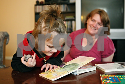Rob Winner – rwinner@shawmedia.com  Abbiggail Cowles, 2, reads a book as her mother Ellen Cowles watches at their Sycamore home Tuesday evening. Abbiggail was diagnosed with autism in July 2011.  Sycamore, Ill. Tuesday, April 24, 2012