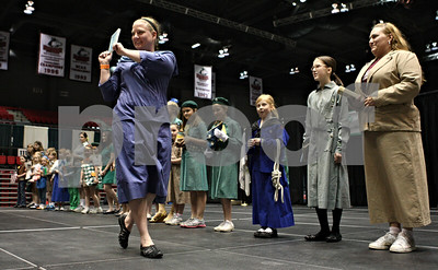 "Rob Winner – rwinner@shawmedia.com  Meg Spires, of West Chicago, holds up ""How Girls Can Help Their Country: Handbook for Girl Scouts,"" while wearing a replica 1913 Girl Scout uniform during a historical fashion show at the Girls Scouts of Northern Illinois Centennial Celebration at the Convocation Center in DeKalb Saturday afternoon."