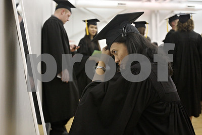Rob Winner – rwinner@shawmedia.com  Accounting major Fransiska Gultom uses a mirror to prepare for the second of three commencements at the Convocation Center in DeKalb Saturday.