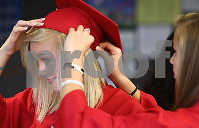 Kyle Bursaw – kbursaw@shawmedia.com  Ally Bretzing helps fellow Indian Creek senior Megan Govig adjust her cap before the graduation ceremony at their high school on Sunday, May 13, 2012.