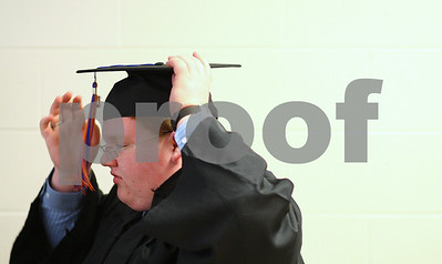 Kyle Bursaw – kbursaw@shawmedia.com  Genoa-Kingston graduating senior Paul VanDerHeyden adjusts his cap in the hallway before the ceremony on Wednesday, May 16, 2012.