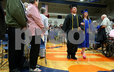 Kyle Bursaw – kbursaw@shawmedia.com  Two of Genoa-Kingston's graduating seniors make their way to their seats during the ceremony on Wednesday, May 16, 2012.