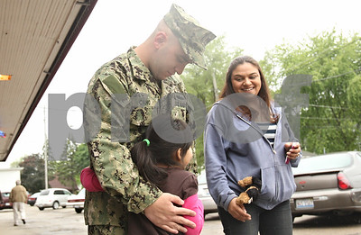 Rob Winner – rwinner@shawmedia.com  Navy GSE3(SW) Justin Cano is hugged by his 5-year-old cousin Yesenia Aspera outside of Sullivan's Tavern in DeKalb before a welcome home celebration Saturday.