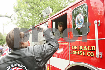 Rob Winner – rwinner@shawmedia.com  Navy GSE3(SW) Justin Cano of DeKalb sits inside a DeKalb fire engine before being escorted to Sullivan's Tavern in DeKalb for a welcome home celebration Saturday. The engine was followed by a group of Warriors' Watch Riders, family and friends.