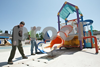 Rob Winner – rwinner@shawmedia.com  DeKalb Park District employees Brad Garrison (left) and Todd Bex discuss the installation of a new water slide for the children's pool area at Hopkins Park Tuesday afternoon.