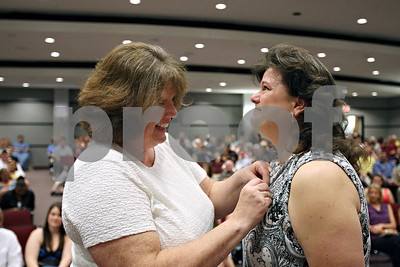 Rob Winner – rwinner@shawmedia.com  Lisa Anger (right) receives her nursing pin from her mentor Sue Allen during a pinning ceremony at Kishwaukee College in Malta Saturday morning.