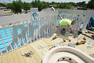 Rob Winner – rwinner@shawmedia.com  DeKalb Park District employee Jeff Zweifel makes repairs to the top deck of the large water slide inside the pool area at Hopkins Park Tuesday afternoon.