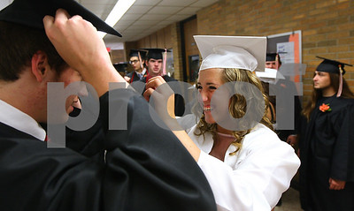 Kyle Bursaw – kbursaw@shawmedia.com  Caitlyn Jennings helps her twin brother A.J. Jennings with his cap before the Sandwich High School graduation on Sunday, May 20, 2012.