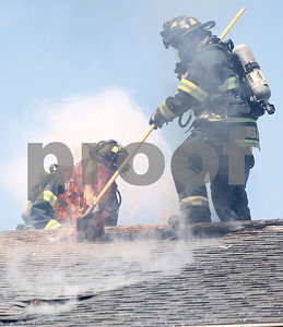 Kyle Bursaw – kbursaw@shawmedia.com  DeKalb firefighters work to open up a hole in the roof of 1057 Ridge Drive in DeKalb, Ill. to extinguish a fire on Monday, May 21, 2012.