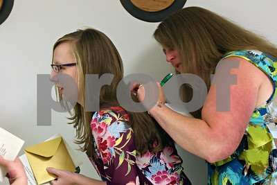 Rob Winner – rwinner@shawmedia.com  Nursing student Stacey Opiela (left) allows Jennifer Aversano to sign a card on her back for Sylvia Baker (not pictured) before their pinning ceremony at Kishwaukee College in Malta Saturday morning.