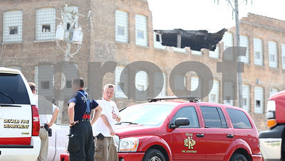 Kyle Bursaw – kbursaw@shawmedia.com  Members of the DeKalb Fire Department talk by a building on Pleasant Street in DeKalb, long known as the Wurlitzer Company, where a portion of the building collapsed on Sunday, May 20, 2012.
