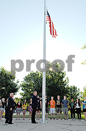 Sycamore High School sophomore Justin Bolander, a member of the Future Farmers of America organization, lowers the flag to half staff Friday during the school's annual Memorial Day observance.  By Nicole Weskerna - nweskerna@shawmedia.com