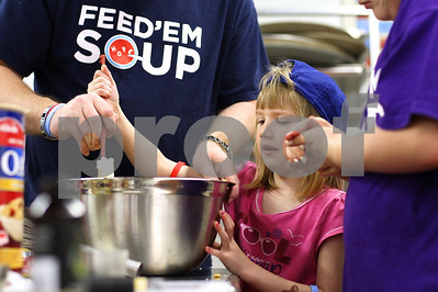 Kyle Bursaw – kbursaw@shawmedia.com  Todd Busch (in Feed'em Soup shirt) helps his daughter Tessa, 4, mix up the ingredients for 'monster cookies' on Tuesday, May 8, 2012 to be served at the Feed'em Soup meal the next day. On Tuesday nights prior to meals, Smith leads a program called 'Baking with Chef Alex' where groups come and learn about working in the kitchen while helping produce baked goods for the meals.