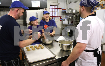 Kyle Bursaw – kbursaw@shawmedia.com  Chef Alex Smith, of Feed'em Soup (right), works with the Busch family including Todd (from left), Emma, 9, and Dawn to bake 300 'monster cookies' on Tuesday, May 8, 2012 to be served at the Feed'em Soup meal the next day. On Tuesday nights prior to meals, Smith leads a program called 'Baking with Chef Alex' where groups come and learn about working in the kitchen while helping produce baked goods for the meals.