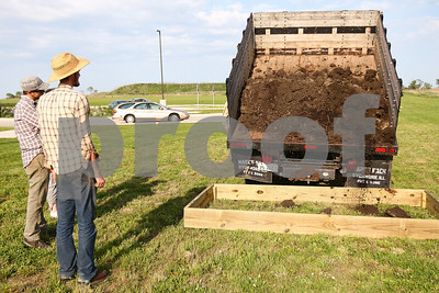Kyle Bursaw – kbursaw@shawmedia.com  Nathan Dettman (from left) and Heath Johnson, members of the DeKalb County Community Garden group, look on as dirt is dumped into one of two garden plots at Cortland Elementary on Friday, May 11, 2012.