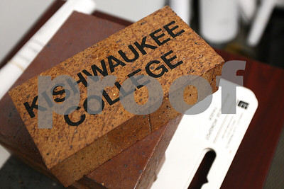 "Kyle Bursaw – kbursaw@shawmedia.com  A 'Kishwaukee College' brick sits in Rob Galick's office at the college. The brick is part of the college's ""Paving the way for the Future of Education!"" program, which sells custom bricks that will line the path to the new front entrance of the college. The size pictured on top cost $100 and one the size of the brick underneath cost $250."
