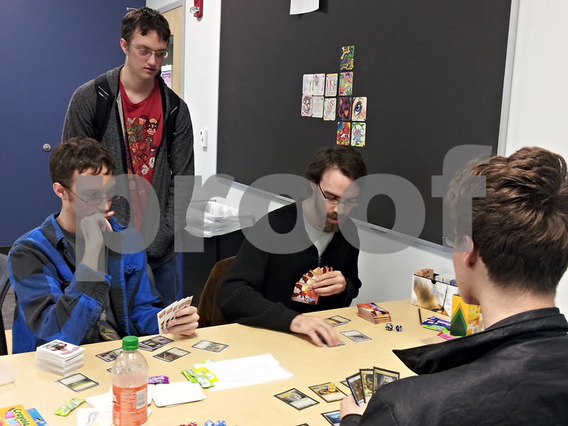 Korey Miller (standing) watches Matthew Miller (left) and Aaron Young (right) play against Corey Elliott in Magic: The Gathering. The first-year Kishwaukee College students were playing in the game room of the college's new student-focused wing.