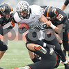 Sean King for the Chronicle<br /> <br /> Kaneland's Dylan Nauert (20) is tackled after the catch by Lincoln-Way West's Samuel Tiberi (29) and Jake Bohne (20) during a Class 5A playoff game in New Lenox, Ill., on Saturday, Nov. 3, 2012. Lincoln-Way West defeated Kaneland, 31-15.