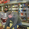 Adric Peccarelli, 23, and Sean Kayes, 32, employees of American Liquors, open boxes containing six-packs of beer. The owner of American Liquors, Louis Schoenburg, is concerned about the effect DeKalb's proposed liquor license overhaul would have on the community.