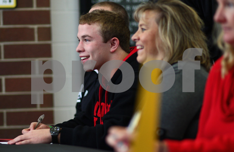 Kyle Bursaw – kbursaw@shawmedia.com<br /> <br /> Sycamore's Austin Culton (left), accompanied by his parents Dana  (pictured, center) and Randy (obscured behind Austin), smiles for a number of cameras at Sycamore High School while signing a letter of intent to wrestle with Northern Illinois University during a signing day event at Sycamore High School on Wednesday, Nov. 14, 2012.