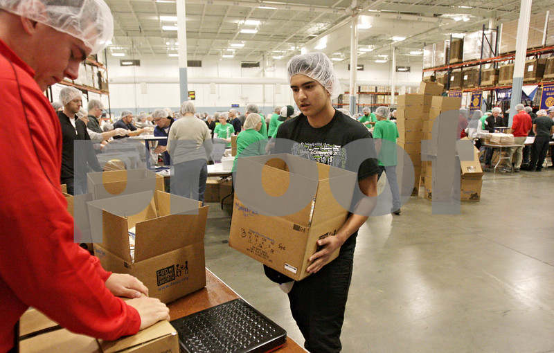 Rob Winner – rwinner@shawmedia.com<br /> <br /> Volunteer David Toledo, 15, of Marengo, carries a box filled with rice packets to a scale to be weighed before shipping during the first shift of the Feed My Starving Children MobilePack event at The Suter Co. Inc. in Sycamore, Ill., Friday, Nov. 16, 2012.
