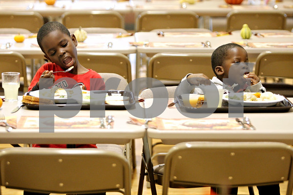 Rob Winner – rwinner@shawmedia.com<br /> <br /> Cousins Emmanuel Saye (left), 5, and Abraham James, 3, both of Sycamore, enjoy their Thanksgiving dinner at the Evangelical Lutheran Church of St. John in Sycamore, Ill., Thursday, Nov. 22, 2012.