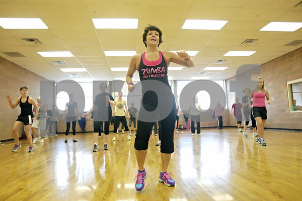 Rob Winner – rwinner@shawmedia.com<br /> <br /> Fitness instructor Jill Farris (front) leads a zumba class during the Be Thankful Workout event at the DeKalb Park District Sports and Recreation Center early Thursday morning. Donations to benefit Ronald McDonald House were accepted as well as non-perishable goods for the Salvation Army's food pantry.