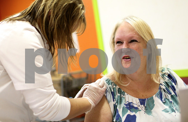 Kyle Bursaw – kbursaw@shawmedia.com<br /> <br /> Walgreen's Pharmacy Manager Amy Elliott (left) preps the arm of Marsha Broude for a free flu shot at the Salvation Army in DeKalb, Ill. on Tuesday, Nov. 20, 2012. Walgreen's offered the flu shots for those picking up food for Thanksgiving meals.