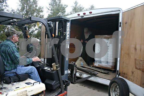 Jeff Engelhardt – jengelhardt@shawmedia.com<br /> Russ Ziegler, of Ideal Industries, loads relief buckets into a trailer as Glen Stewart (in the trailer) and Bud Ritter (left), of United Methodist Committee on Relief, organize them.