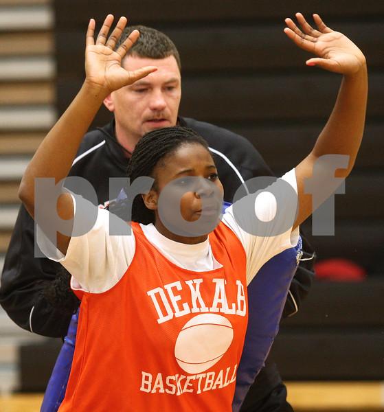 Kyle Bursaw – kbursaw@shawmedia.com<br /> <br /> DeKalb coach Chris Davenport plays defender during a drill with senior Janay Wright at practice in DeKalb High School on Tuesday, Oct. 30, 2012.