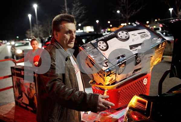 Kyle Bursaw – kbursaw@shawmedia.com<br /> <br /> Quinn Newborn assesses how to fit a 50-inch television, a Kid Trax Ride On Mercedes and a princess-themed toy kit (seen on the carts behind him) into his vehicle outside Target in DeKalb, Ill. on Thursday, Nov. 22, 2012. Newborn couldn't quite fit everything into the car and his wife Sheri drove back to their Genoa home without him.