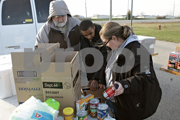 Rob Winner – rwinner@shawmedia.com<br /> <br /> Scout Master Cliff Golden (from left to right) Travis deOliveira, 14, and deOliverira's mother, Michele Gray, sort items to benefit victims of Hurricane Sandy during a Boy Scout Troop 33 supply drive outside Algus Packaging, Inc. in DeKalb,   Ill., Saturday, Nov. 17, 2012. Scout members of Troop 33 will be traveling to New Jersey on Tuesday to deliver the supplies collected during Saturday's drive.