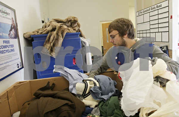 Rob Winner – rwinner@shawmedia.com<br /> <br /> Employee Jake Michael removes plastic bags from a bin filled with donated clothing at Goodwill in DeKalb, Ill., Saturday, Nov. 24, 2012.