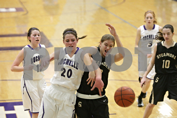 Rob Winner – rwinner@shawmedia.com<br /> <br /> Rochelle's Abby Gould (20) and Sycamore's Baylee Foresman struggle for a ball under the Spartans' basket during the second quarter in Rochelle, Ill., Friday, Nov. 30, 2012. Rochelle defeated Sycamore, 52-49.